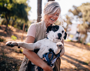 active midlife woman playing with dog